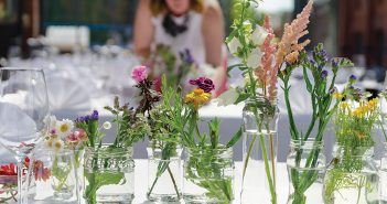 flowers in glass jars on white table in sun
