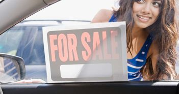 """woman looking in car window at a sign that says """"for sale"""""""