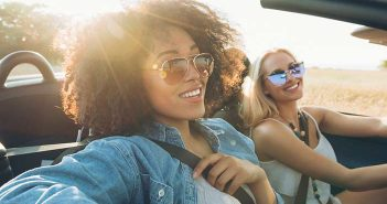 two women driving a convertible car wearing sunglasses