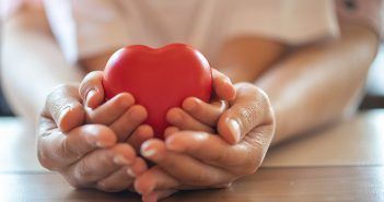 Hands wrapping around a heart
