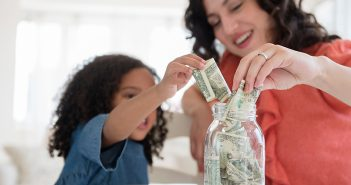 mom and daughter putting money in a jar