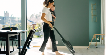 Girl with baby vacuuming the floor